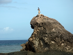 Man dressed in tribal dress greeting us on Warrior Rock; Barefoot Kuata Island