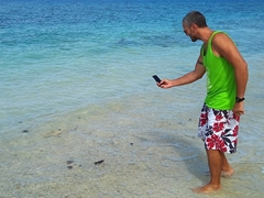 Robby spots a black tip reef shark swimming by the shoreline