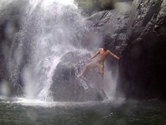Luke attempting to climb up a rock under the powerful waterfall