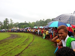 Despite the rain, the field is crowded with excited students cheering their friends on