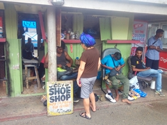 Ann getting her shoe fixed at a shoe shop in Suva