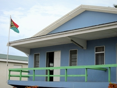 Vanuatu flag next to this pastel blue house