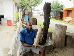 A wood carver proudly shows off his latest piece; Port Vila