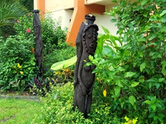 Carved totem poles outside Hotel Santo; Luganville
