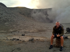 Robby smiles at the crater of the volcano