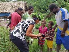 Becky showing village kids their photo