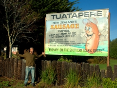 "Robby next to the Tuatapere ""Sausage Capital of New Zealand"" billboard"
