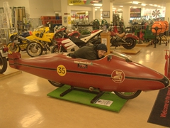 Robby striking a pose inside the 'World's Fastest Indian'; E. Hayes & Sons