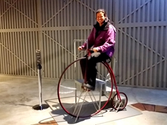Becky riding a penny-farthing (high wheeler); Toitū Otago Settlers Museum