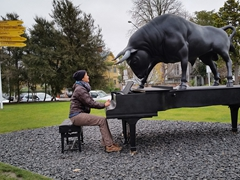 Becky playing the piano while a bronze bull looks on; Christchurch Art Gallery