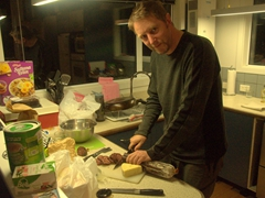 Damien slicing up some delicious venison sausage at his Lake Clearwater bach rental