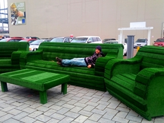 Robby lounging on an oversized armchair made from astro turf; Christchurch