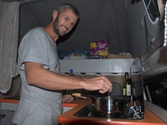 Robby preparing dinner in our camper van