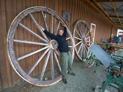 Robby next to a massive wagon wheel; Founders Heritage Park