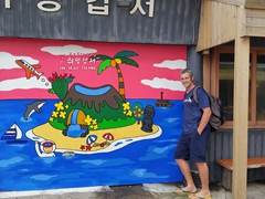 Robby next to a colorful Jeju map