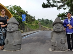 Becky and Chi Xuan pose next to guardian stone statues, protectors of Jeju Island; Yongduam Rock