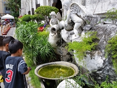 Children fascinated by the fountain of the Church and Convent of Santo Nino