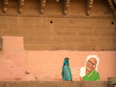 A woman walks past a mural painted on one of Varanasi's many ghats