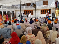 Sikh visitors listen avidly to a religious address; Golden Temple