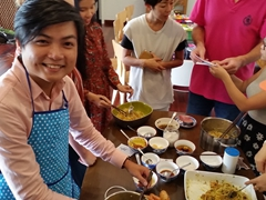 "Tuấn Anh smiles in an apron as we prepare ""Cá thu nướng nghệ"" (grilled tuna fish)"
