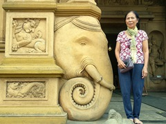 Di Phuong stands next to a massive elephant carving; Kelaniya Temple
