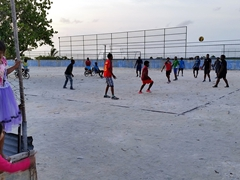 Two girls watching the boys play volleyball; Dhiggaru Island