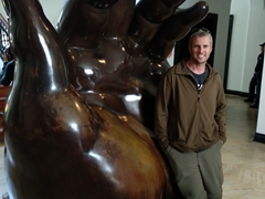 Robby poses next to the hand statue; Botero Museum