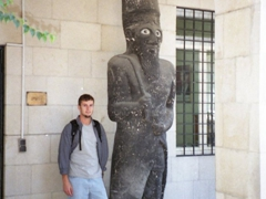 Robby poses next to an Assyrian  statue at the National Museum entrance; Damascus