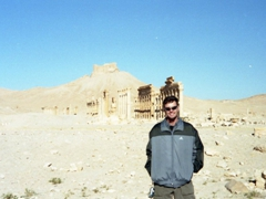 """Robby standing in front of the columns of the inner court of the Temple of Ba'al with the 13th century Fakhr-al-Din al-Ma'ani Castle, sometimes also referred to as """"Qala'at ibn Maan"""" dominating the hilltop behind"""