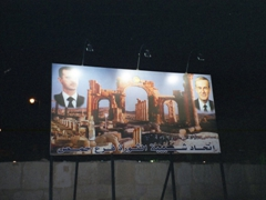 Night shot of a billboard showcasing President Bashar al-Assad along with his father Hafez al-Assad endorsing the ancient city of Palmyra