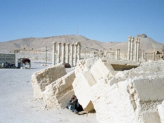 A local tries to find some shade under the massive ruins of Palmyra during the mid-day sun
