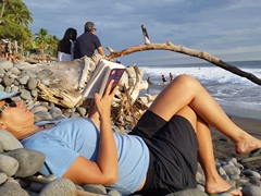 Reading on the rocky beach at El Tunco