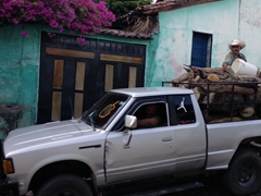 Hitching a ride on the back of a pickup truck filled with logs; Suchitoto