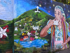 Elder woman sipping on coffee; Ataco mural scene