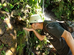 Robby drinking fresh water from a crocodile spout; Juayua's seven waterfalls hike