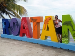 Posing by the Roatan sign