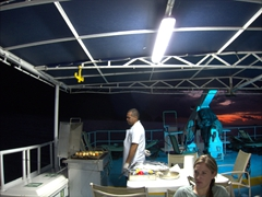 The chef grills meat and vegetables on the top deck for BBQ night