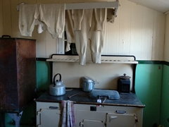 Replica of wet laundry hanging over the stove to dry; Port Lockroy basecamp