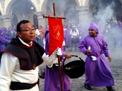 A white clad banner carrier stands out amongst the purple robed cucuruchos (carriers) during the Lent procession; Antiigua