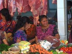 Indigenous Guatemalan women in traditional clothing shopping at the Sunday market; Panajachel