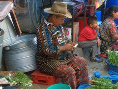 A man in traditional clothes counts his money; Panajachel market