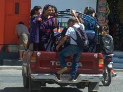 Locals ride a pick up truck colectivo; Panajachel