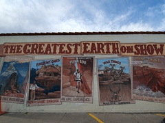 """The Greatest Earth on Show"" mural painted on the side of a car wash; Kanab"