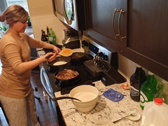 Ally making a Canadian feast for breakfast - sausage links, pancakes with home made maple syrup and coffee/tea