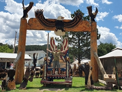 Robby standing on a massive wooden carved chair at Jordan Dahl's chainsaw art; Hill City