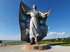 Becky at the base of the Dignity statue, a 50 foot stainless steel statue overlooking the Missouri River near Chamberlain, South Dakota