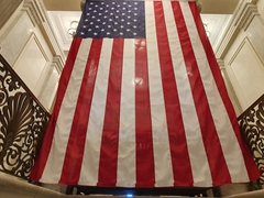Massive US flag above an entrance to the capitol rotunda