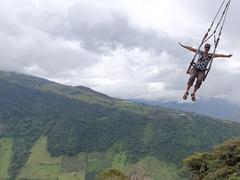 Swinging over the edge of a mountain at La Casa del Arbol; Banos