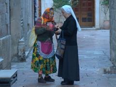 A nun gives a beggar some money; Old Kotor