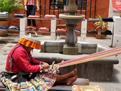 Local lady demonstrating using alpaca fiber to weave a scarf; Arequipa